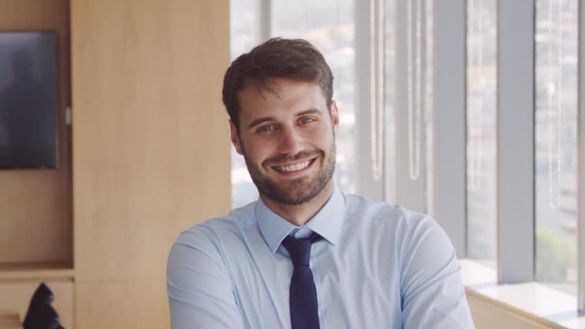 Portrait Of Businessman In Office Walking Towards Camera