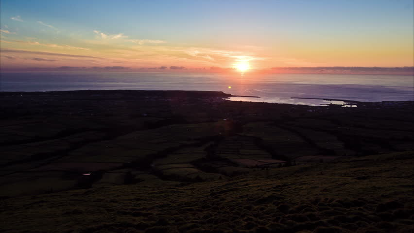 Timelapse of the sun rising over the Atlantic Ocean and lighting fields in Praia da Vitoria, a city in the island of Terceira, in the archipelago of the Azores, Portugal.
