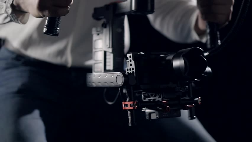 Smooth movement of the camera in the protective cage installed on the stabilizer in the hands of the operator focusing on the screen recorder. | Shutterstock HD Video #26617319