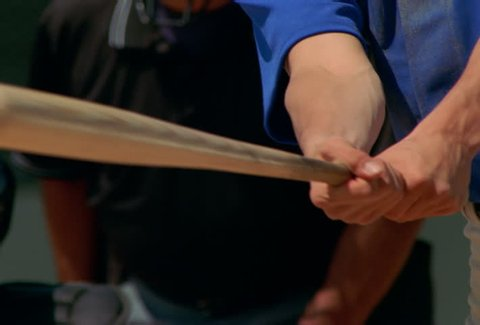 Close-up hands and arms of batter swinging bat in slow motion