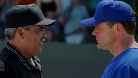 Close-up head-to-head profiles of baseball coach and umpire arguing a call
