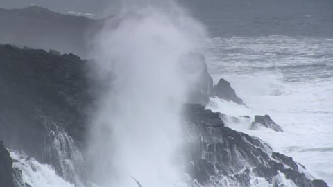 Spray from crashing waves drifting over high rocky outcrops