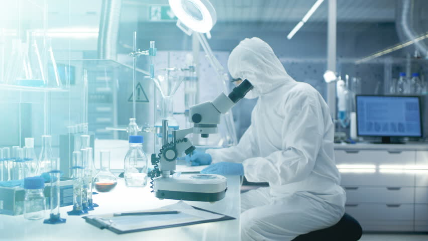 In the Secure High Level Laboratory Scientists in a Coverall Conducting a Research. Chemist Adjusts Samples in a Petri Dish with Pincers and then Examines Them Under Microscope.RED Cinema Camera | Shutterstock HD Video #26643439