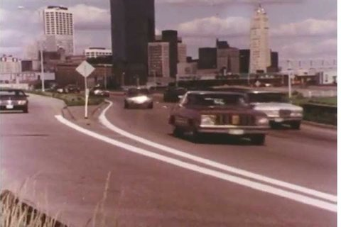 1980s: Cars being driven on the highway, parallel parking and leaving an automobile dealership are shown, in 1983.