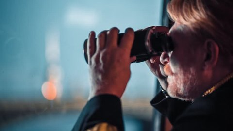 Ship captain with a binoculars looking at the river