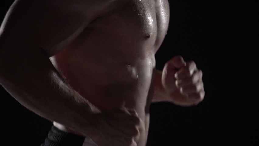 Muscular man running in profile, close up torso