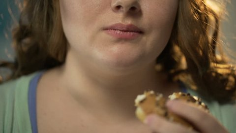 Plump woman biting donut and chewing it, overeating sweet pastry, face closeup. Fat female addicted to junkfood, high sugar level, nutrition diet failure. Hungry person having unhealthy snack