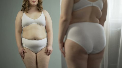 Girl looking in mirror at big belly and fat hips, needs healthy weightloss diet