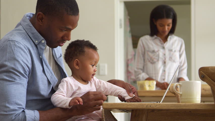 Father And Baby Daughter Use Laptop As Mother Prepares Meal | Shutterstock HD Video #26692699