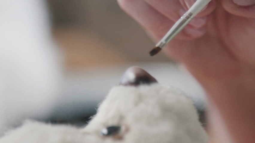 Fine brush for drawing: the nose of a soft toy. Creation of teddy bear in vintage style. The master draws a nose for a teddy bear in an old-fashioned style. Favorite toy of children is a teddy bear