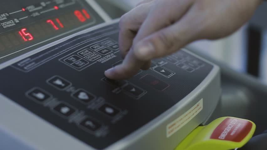 The man selects the loading mode on the scoreboard of the treadmill | Shutterstock HD Video #26704336