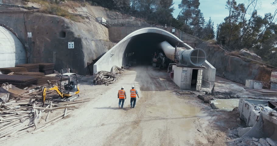 Aerial footage of a tunnel construction site with workers and equipment