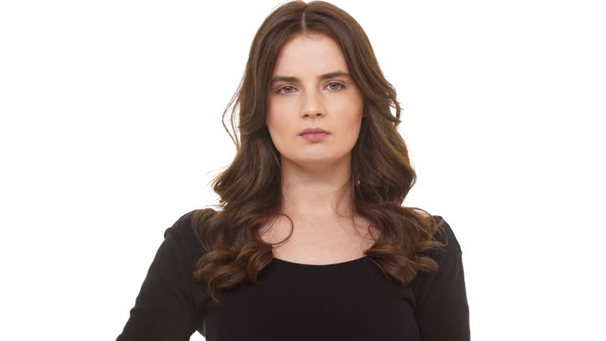 Unhappy Caucasian brunette female in black dress standing on white background and shaking head in disbelief | Shutterstock HD Video #26711299