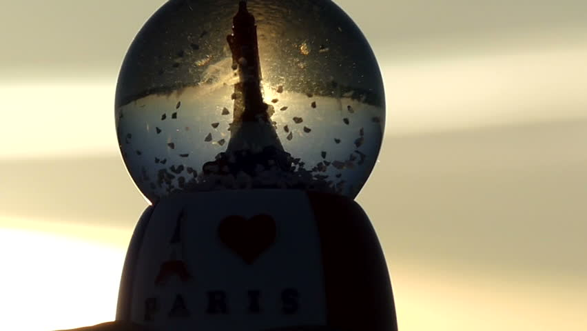 "A Toy With Abstractly Moving Sparkles Inside and the Inscription ""paris"" is Opposite the Sun. Sunlight Beautifully Penetrates Through a Transparent Toy. 