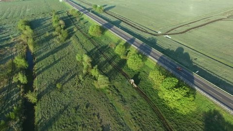 4K aerial footage of a tractor riding on a field road along asfalt road
