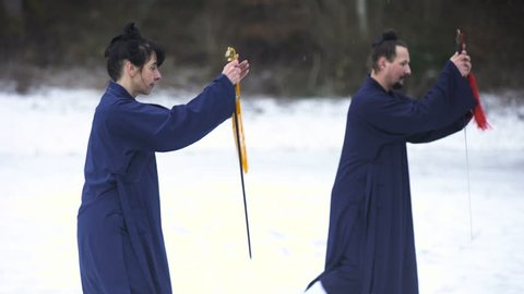 Training Martial Arts Sword Techniques in Snow 4K. Long shot of two person in focus, man and woman in blue kimono train in middle of snow. Medium shot from knees up.