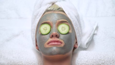 Attractive young blonde model wearing face mask with cucumber on her eyes and towel on her head