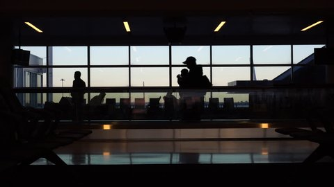 Airport terminal people silhouette against morning sunrise out window. Walk through security gate area to wait for flight departure 4K stock video