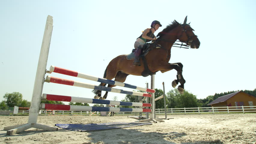 SLOW MOTION, CLOSE UP, LOW ANGLE VIEW: Girl riding beautiful dark brown gelding on the jumping show competition. Big horse knocking down the rail and failing when trying to jump over the hurdle #26802409