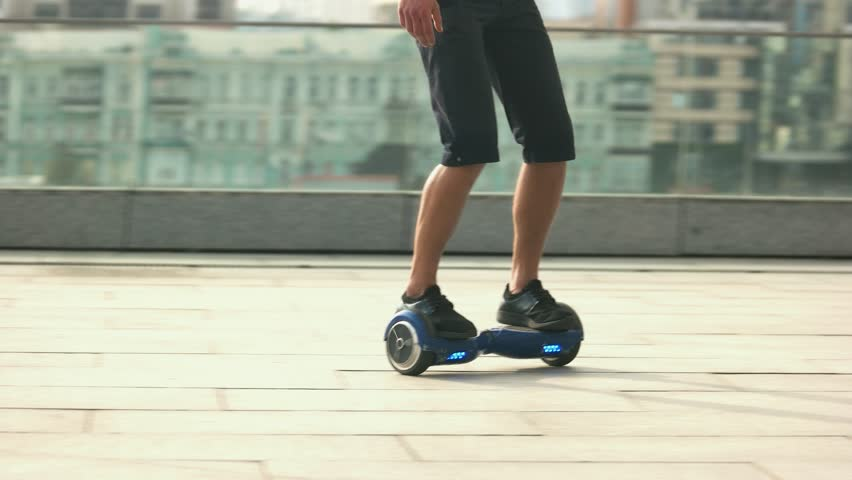 Male legs on hoverboard. Mini segway in motion. Best self balancing scooters.