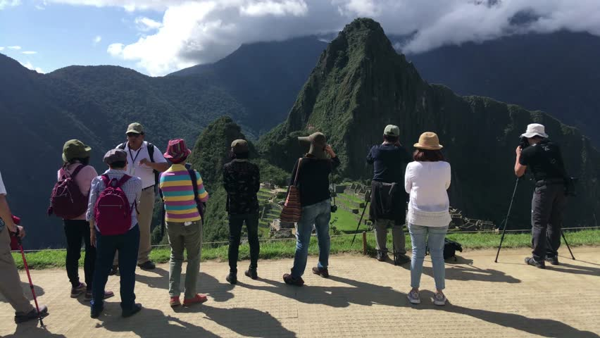MACHU PICCHU, PERU - APR 10, 2017: Tourists at Machu Picchu, the lost city of the Andes, It is located above the Sacred Valley northwest of Cuzco, Machupicchu District, Urubamba, Cusco Region, Peru.