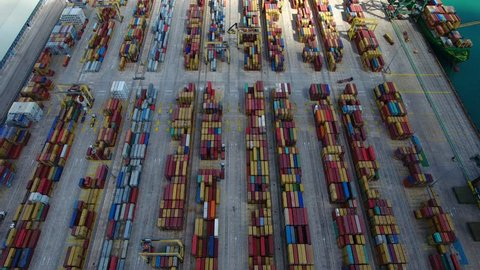 Aerial 4k cinematic view. Flying above the Industrial port with containers ship and moving trucks.
