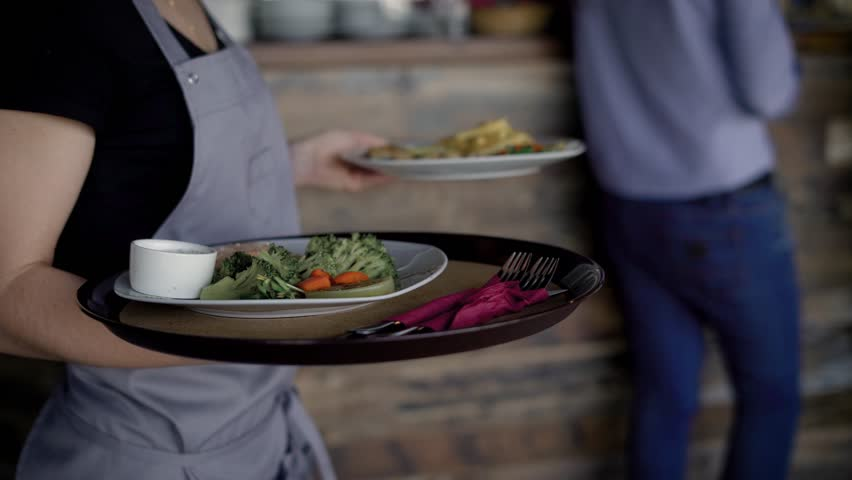 Crop shot of waiter delivering food. Crop faceless shot of server delivering order.