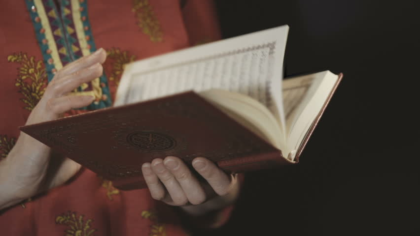 Women's hands leaf through the pages of the Koran