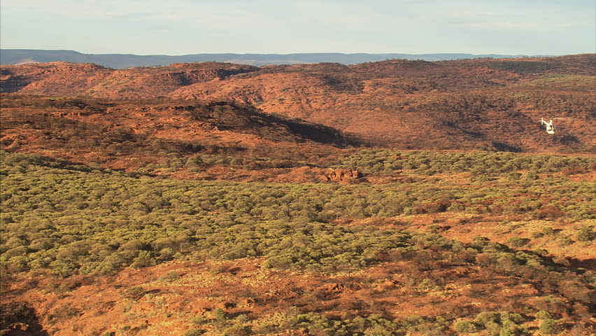 Flying over Australian Outback in the Northern Territory near Alice Springs; helicopter at right of frame as clip begins