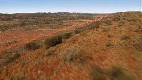 Flying over a ridge top and crossing a red dirt road in the lonely Outback west of Alice Springs, Australia