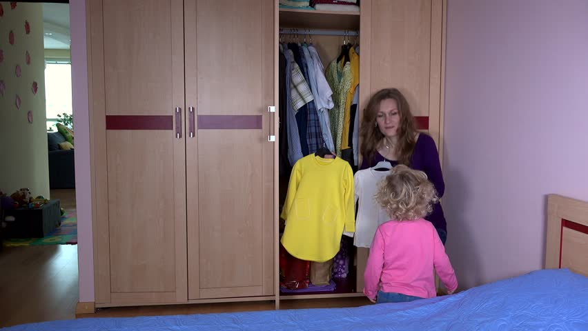 Cute woman with daughter girl take clothes from closet and measure. Preparing for party. Static shot. 4K UHD