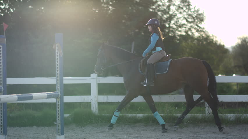 SLOW MOTION CLOSE UP: Young girl horseback riding beautiful chestnut mare in outdoor riding arena during the sunny summer vacations. Horse with a child rider trotting in sandy manege inside the corral