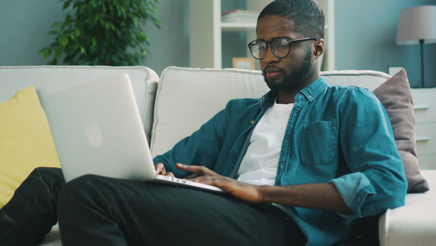 Attractive african man in glasses sitting on the sofa using laptop at home on living background for chatting with friends. Indoor. | Shutterstock HD Video #26912533