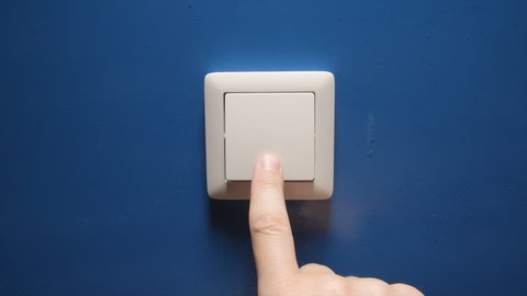 Human hand turn off a power button on a blue wall
