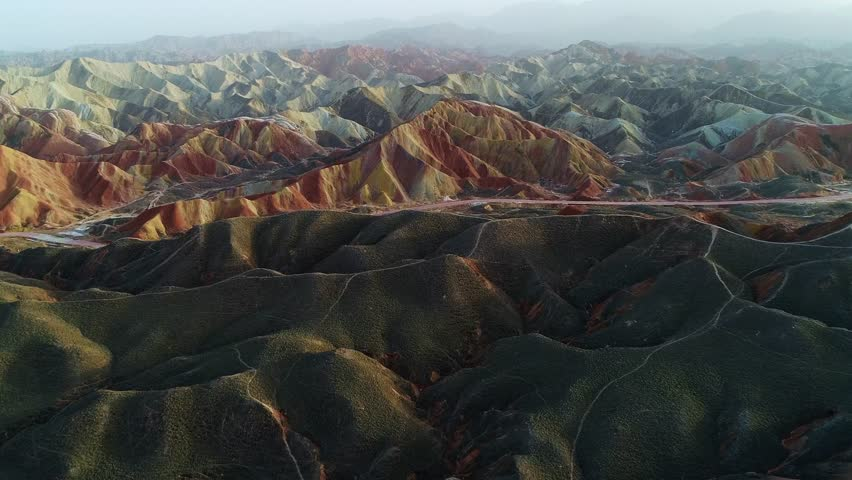 Approaching one of the most beautiful rainbow mountains in Zhangye National Geopark, part 3 of a continuous 3 part series. Aerial view on grass-covered sandstone hills in front of a colorful mountain   Shutterstock HD Video #26918737