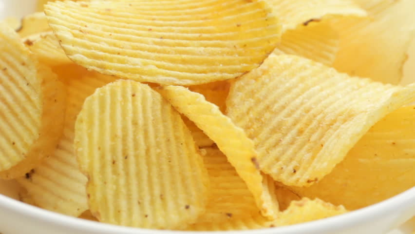 Rotate Unhealthy Harmful food, yellow delicious Potato ribbed crispy chips randomly lying on a white table background, close-up footage moving | Shutterstock HD Video #26931673
