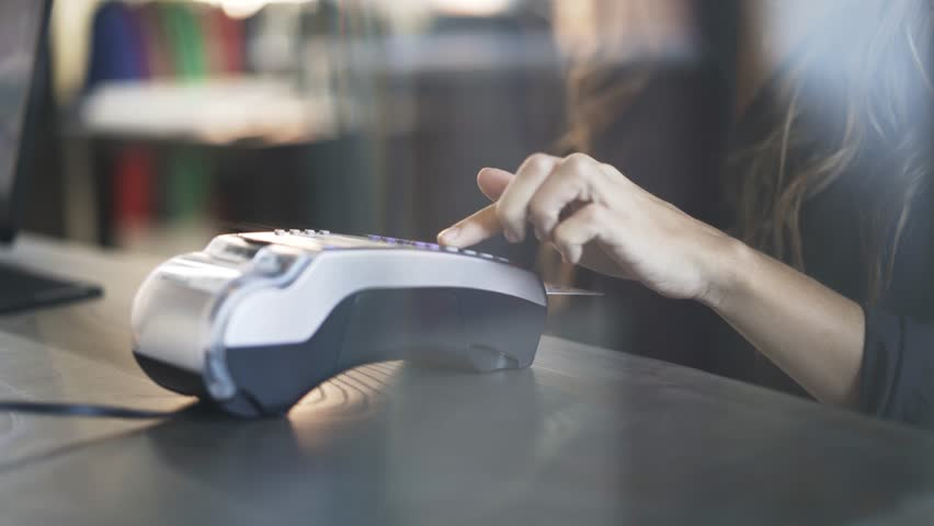 Close up of woman s hand paying with a credit card in a store and taking her purchase. Locked down real time close up shot