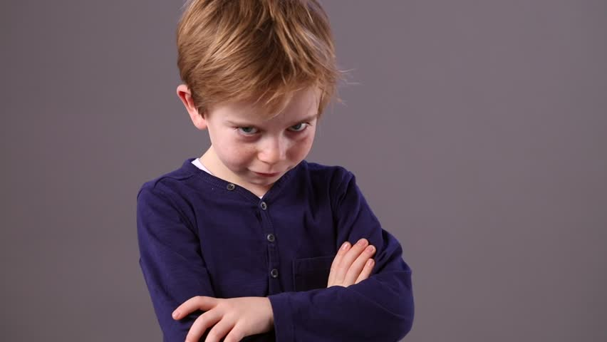 mischievous young 6-year old boy shaking his head and turning his back to refuse with a cheeky pouting smile and sulking body language, grey background indoor