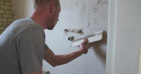 Plasterer plastering a wall with pipelines for water supply in a bathroom renovation, medium shot