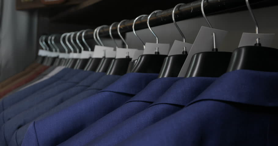 Men's suit at tailor's shop. Men's hands choose a jacket in their wardrobe. Male choosing | Shutterstock HD Video #26970589