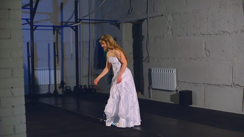 Beautiful and muscular blonde bride in a wedding dress doing exercise with weight | Shutterstock HD Video #26977579