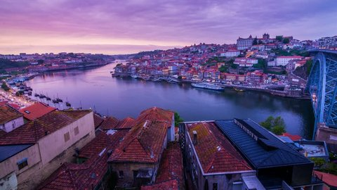 Amazing Porto Timelapse at sunset, old city with river Douro in the foreground. Boats passing by with the Arrabida bridge in the distance and the Dom Luis bridge on the right turning on the lights.
