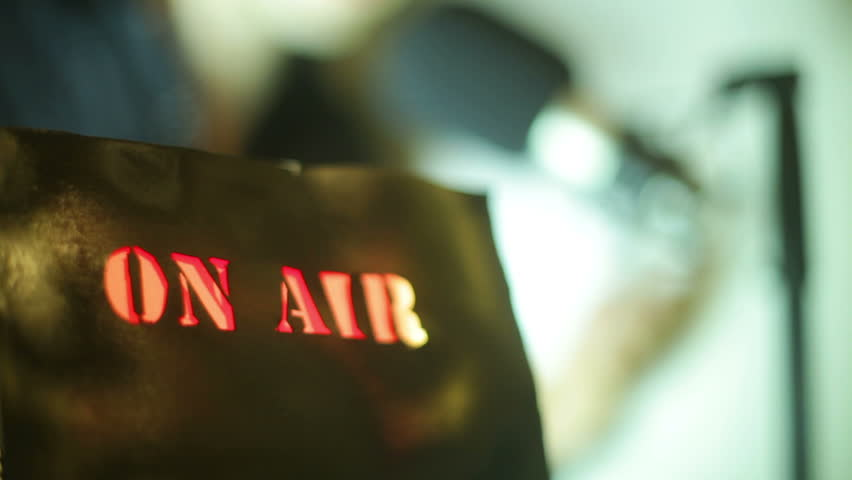 On air sign with a radio/tv announcer in the background