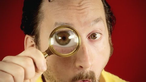 A funny ugly man looking at the camera with a magnifying lens (a detective / private eye), searching for valued information.