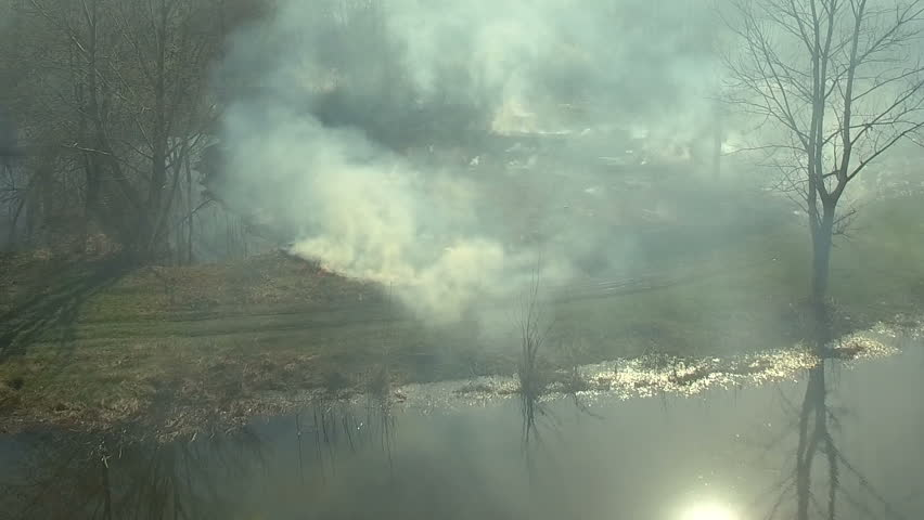 Aerial view of forest fire. Burning grass and bushes. Drone moving forward through the smoke.