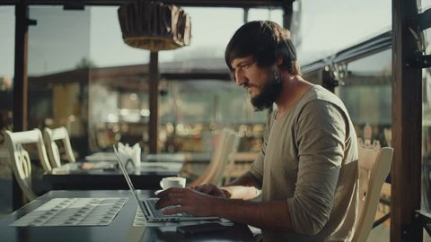 Bearded man freelancer very happy and rejoices sitting in front of laptop in cafe
