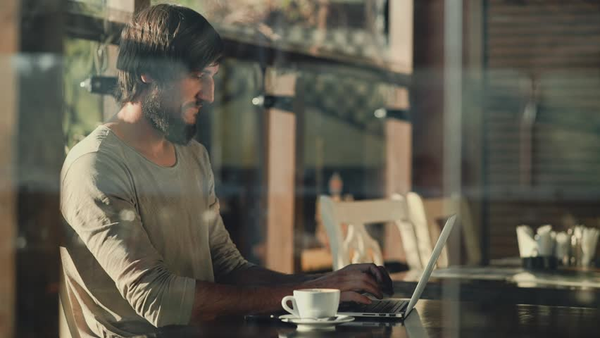 Joyful Young bearded man freelancer sitting and typing in front of laptop in cafe | Shutterstock HD Video #27045919