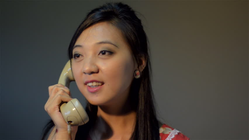 Vintage dressed young Asian woman having an argument on the phone and hangs up - tracking shot.