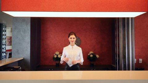 Receptionist greeting hotel guest, giving room key. 4K.