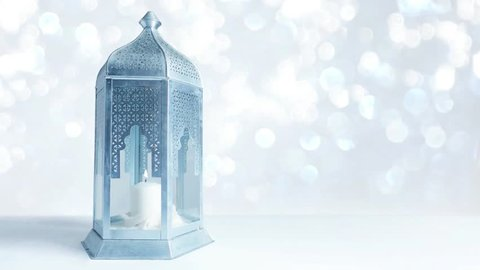 Arabic ornamental lantern with burning candle and glittering silver and blue background with bokeh lights. Loopable Ramadan HD footage.